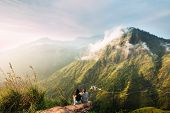 The Couple Greets The Sunrise In The Mountains. Man And Woman In The Mountains. Wedding Travel. The  poster