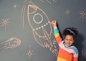 African-american Child Playing With Chalk Rocket Drawing On Grey Background poster