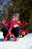 pic of toboggan  - Happy friends in winterwear tobogganing in park - JPG