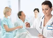 stock photo of work crew  - Doctor recording information to electronic tablet at patients bed - JPG