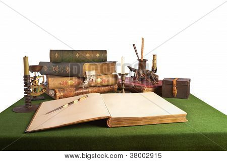 Desk with an open book and old stationery. Isolated onwhite.