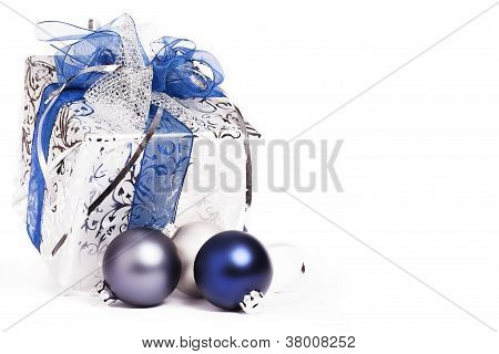 silver christmas present with blue ribbons and blue and silver christmas balls
