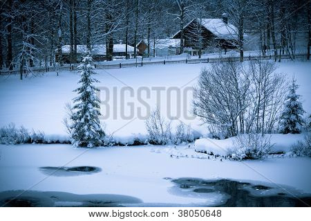 Snowy Alpine House And Frozen River In The Woods