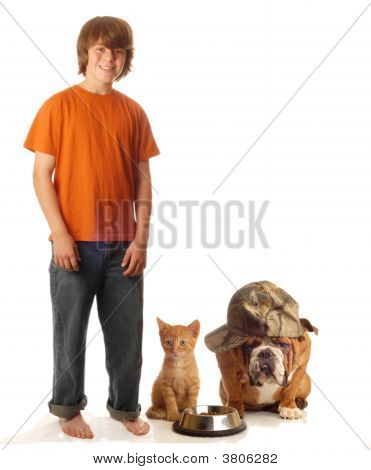 Teen Boy With Dog And Cat At Food Dish