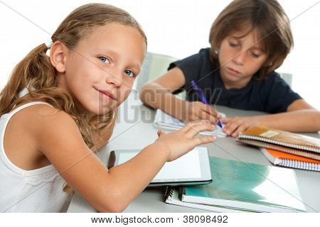 Young Kids Doing Schoolwork Together At Desk.