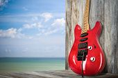 stock photo of stratocaster  - A red old guitar on a dock over the sea - JPG