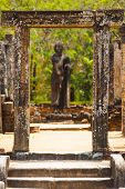 stock photo of quadrangles  - An ancient gate frames a Buddha statue at the quadrangle among the old kingdom capitol ruins of Polonnaruwa Sri Lanka - JPG