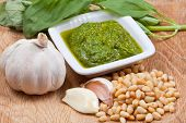 stock photo of pesto sauce  - italian pesto sauce with ingredient on wooden board - JPG