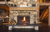 stock photo of log cabin  - Rustic Cabin Interior with Inviting Fireplace Burning - JPG