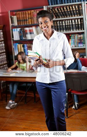 Portrait of happy African American librarian holding books while standing in library with students in background