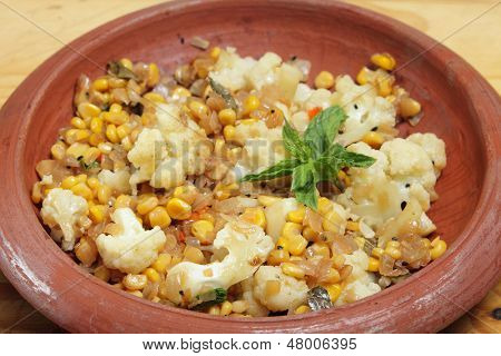 Homemade balti sweetcorn and cauliflower curry in an Indian terracotta bowl