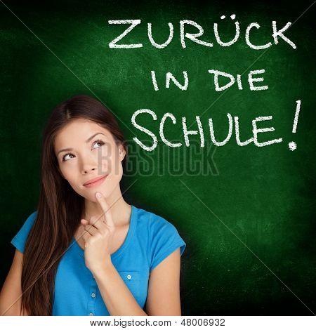 Zuruck in die Schule - German college university student woman thinking Back to School written in German on blackboard by female on green chalkboard. German language at college or high school.