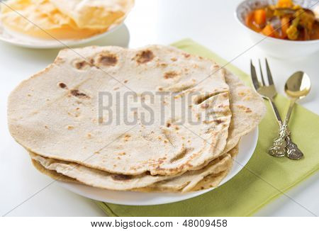 Chapatti roti or Flat bread, papadom and curry dhal. Indian food on dining table.