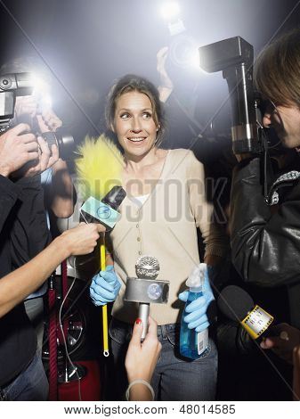 Middle aged woman with cleaning equipment being photographed by paparazzi
