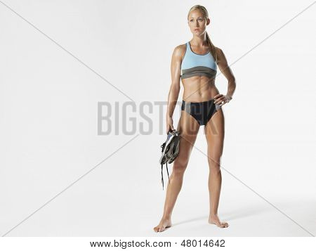 Full length of a serious female athlete holding shoes against white background