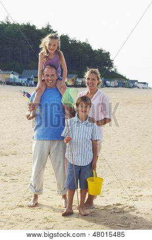 Full length portrait of a family standing on sand at beach