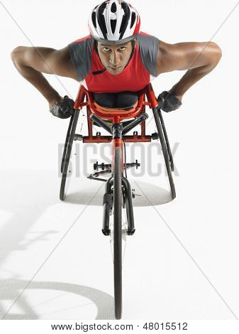 Portrait of a confident paraplegic cycler against white background