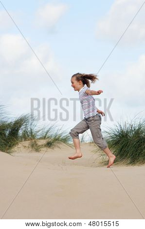 Full length side view of a young girl running on sand at beach