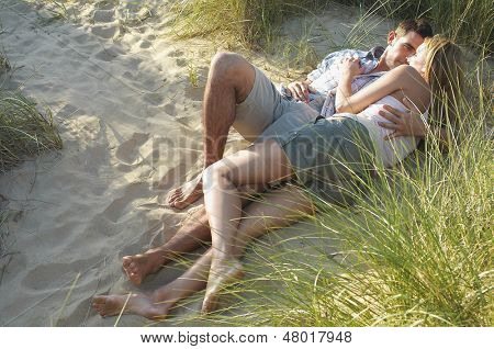 Young couple lying and embracing in secluded spot at beach