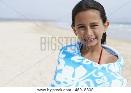 Portrait of cute little preadolescent girl wrapped in towel standing at beach