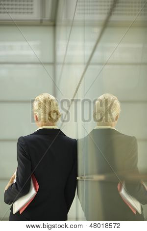 Rear view of young businesswoman leaning against glass partition in office