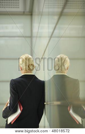Vista posterior de la joven empresaria apoyado contra la partición de cristal en la oficina