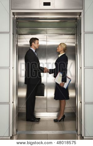 Profile shot of businessman and businesswoman shaking hands in elevator