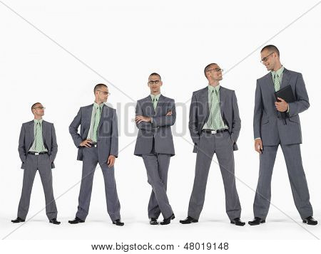Row of businessmen in ascending order of height against white background