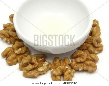 Walnut Oil In A Bowl Of Chinaware Surrounded By Walnuts