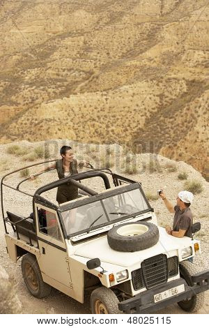 Young man taking photograph of woman in four-wheel-drive car on edge of cliff