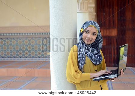 Young asian muslim woman in head scarf with happy pose