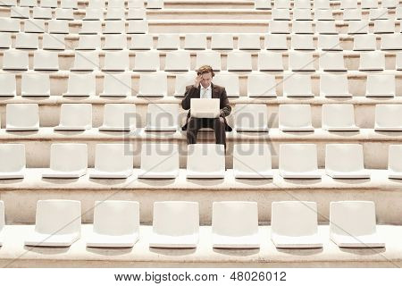 Confused middle aged businessman working on laptop while sitting alone in center of empty auditorium outdoors