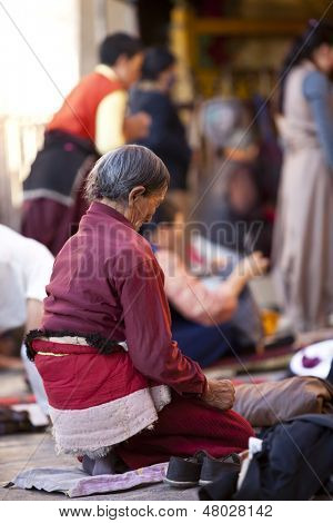 LHASA, TIBET-OCTOBER 08: An old female Tibetan buddhist pilgrim is kneeling and praying in front of Jokhang Temple on October 08, 2011 in Lhasa, Tibet.