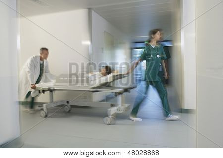 Medical workers moving patient on gurney through hospital corridor