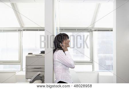 Vista lateral de feliz joven empresaria mediante teléfono móvil apoyado en la partición en la oficina