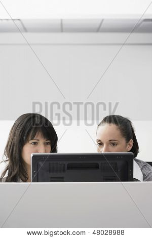 Young businesswomen using computer in office cubicle