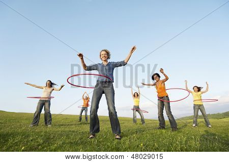 Full length of happy female friends playing with hula hoop against sky in park