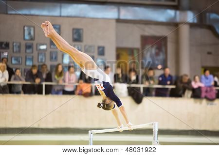 MOSCOW - DEC 15: Young girl on the crossbar perform in Hall Dynamo Stadium at the XIX International Gymnastics Tournament for the Cup of Voronin on December 15, 2012 in Moscow, Russia.