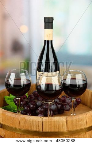 Composition of wine bottle, glasses and  grape, on wooden tray, on bright background