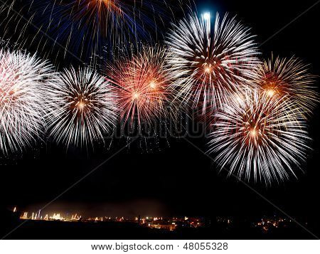Malta, Colorfull fireworks explosion in the dark sky on the left side with the village silouthe on t