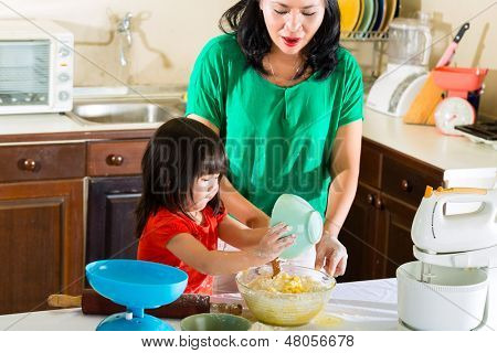 Indonesian Asian Little girl and her mother in the kitchen bake a cake together