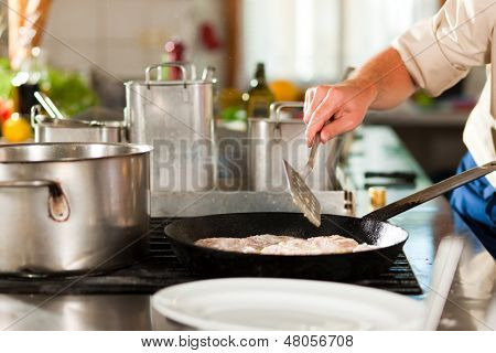 Close up of chefs in a commercial restaurant or hotel kitchen working, they are preparing an fish fillet