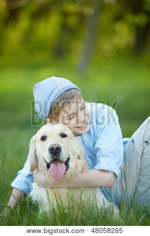 Portrait of cute lad embracing his fluffy friend and laughing