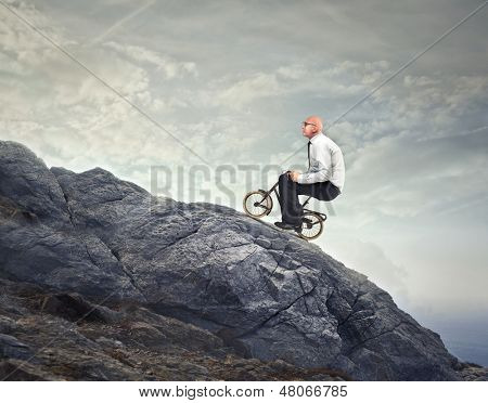 businessman goes with the bike on the rocks uphill