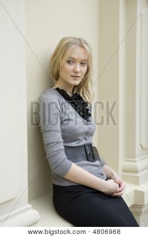 Young Serious Blond Woman At White Wall