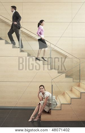 Young businesswoman looking away while using cellphone with colleagues climbing stairs in office