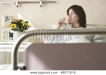 Female patient drinking water in the hospital bed