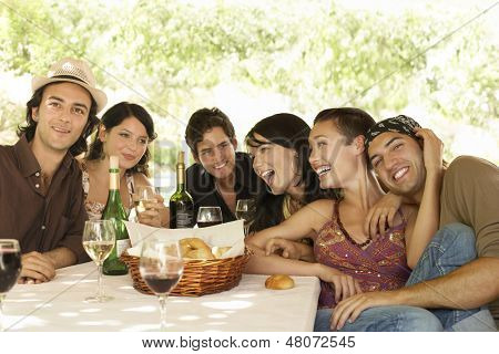 Portrait of young friends with drinks and bread basket at table enjoying party