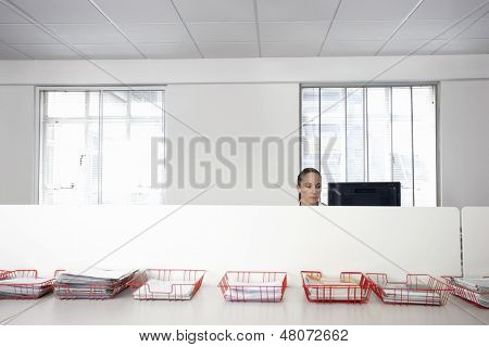 Businesswoman using computer in office cubicle behind trays with documents