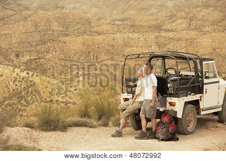 Middle aged couple in back of four-wheel-drive car on cliff edge in desert